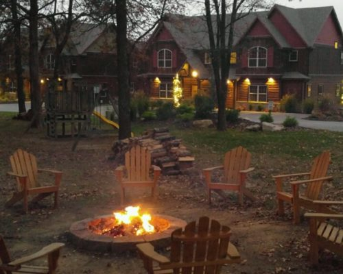 Wood adirondack chairs surrounding a fire pit with lodges in the background